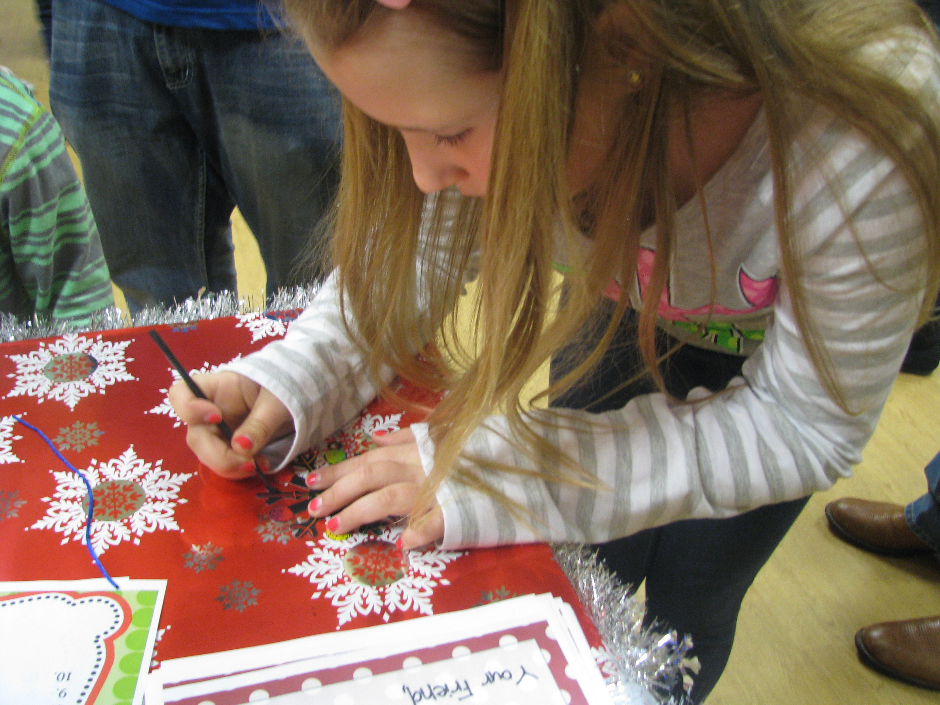 Young girl signing Christmas Cards