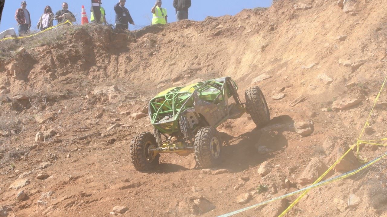 Green off-road vehicle climbing dirt hillside