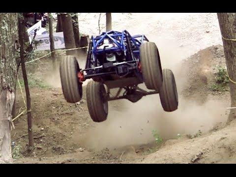 Blue off-road vehicle jumping a dirt ramp