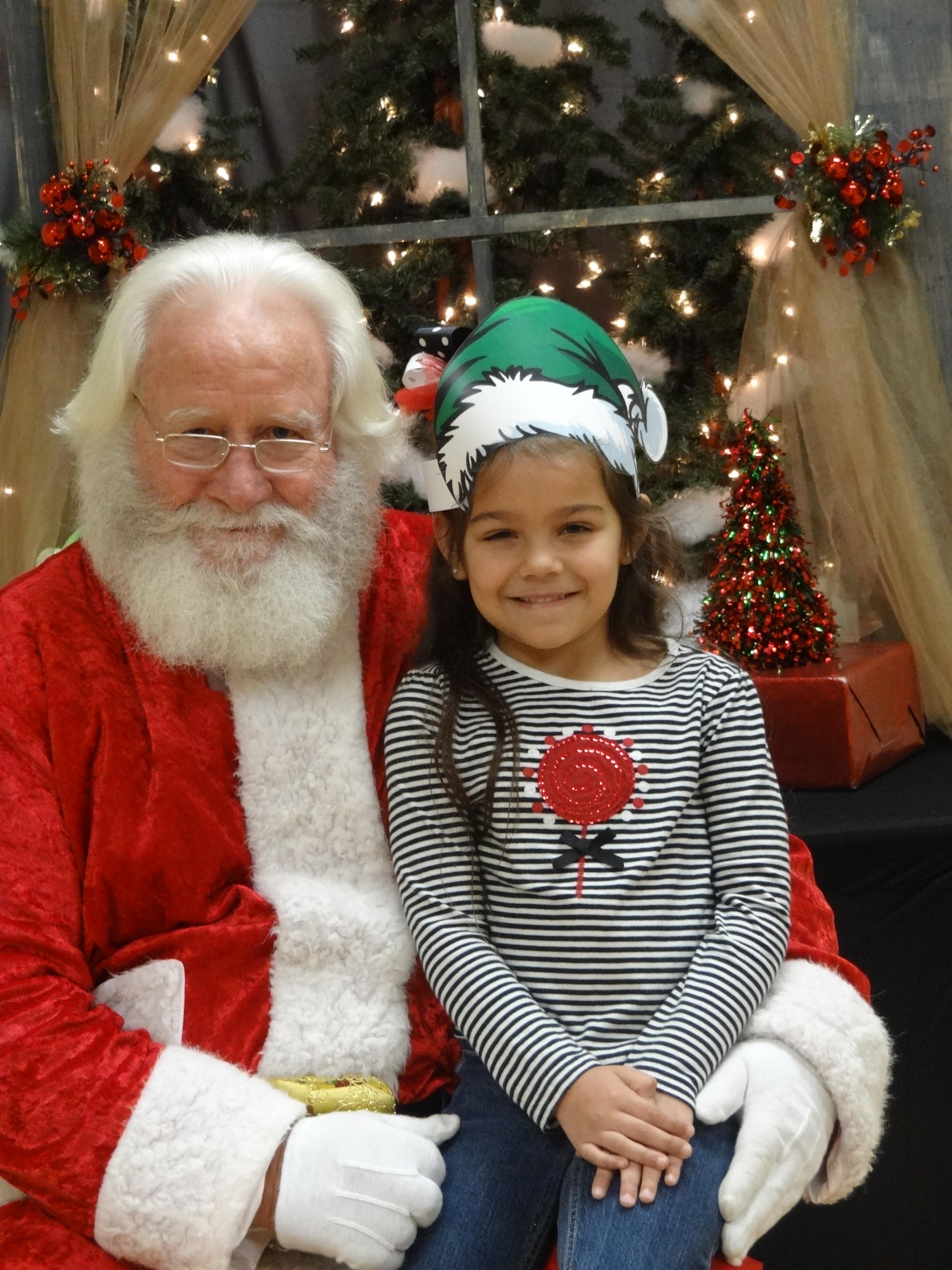 Young girl with elf hat sitting with Santa